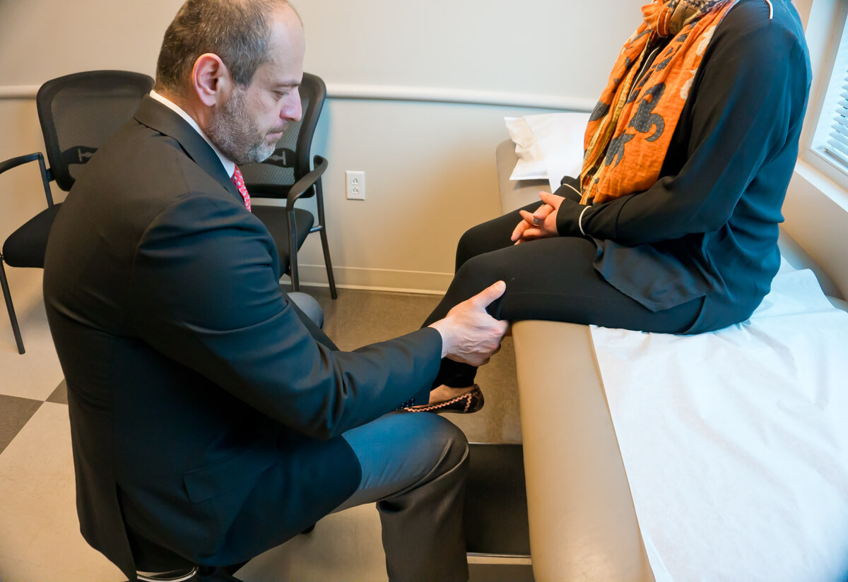 A doctor looking at a patients' knee joint